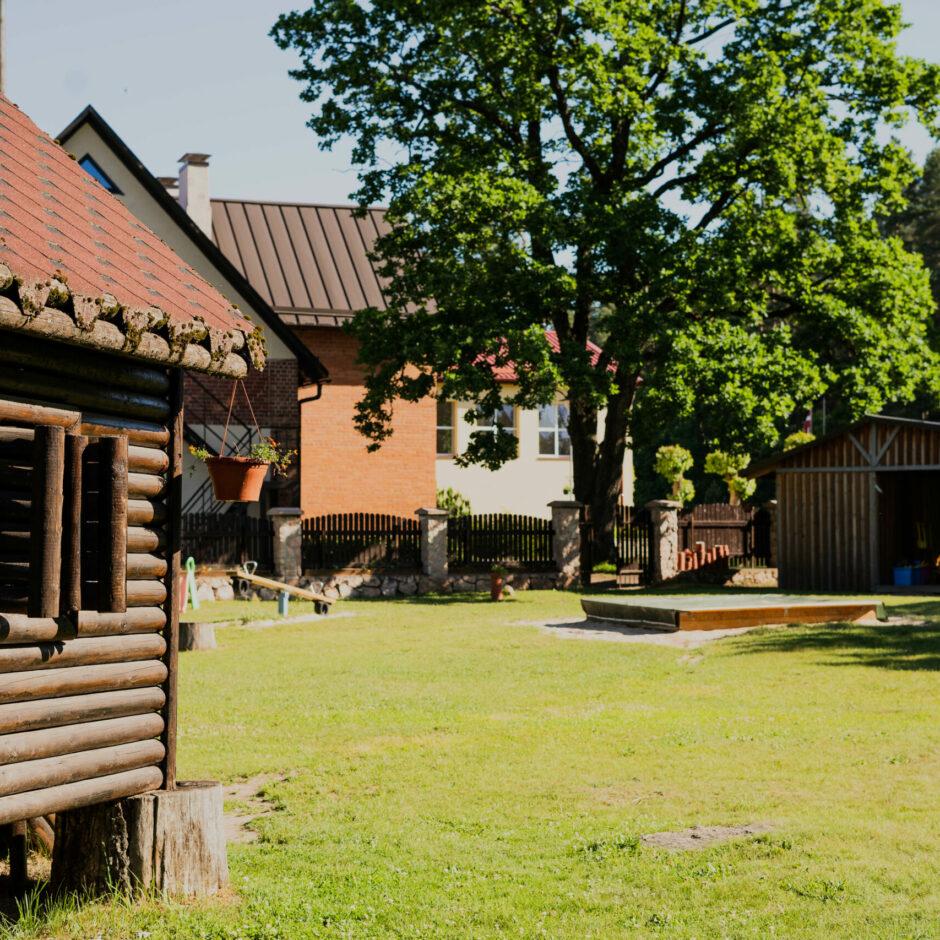 Pirmsskolas rotaļu laukums ar koka namiņu, smilškasti, nojumi un lielu ozolu laukuma malā.