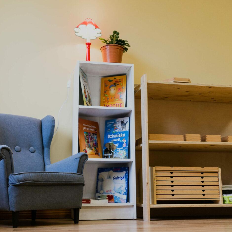 Lasīšanas stūrītis ar grāmatu plauktu un ērtu krēslu.