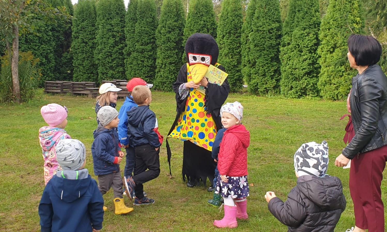 Pirmsskolas bērni āra laukumā kopā ar grupas skolotāju un maskā tērptu